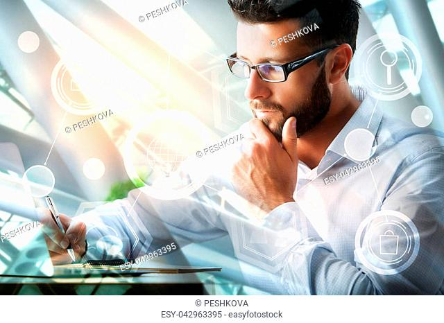Side view of young european businessman using laptop and doing paperwork on abstract city background with sunlight. Accounting and finance concept