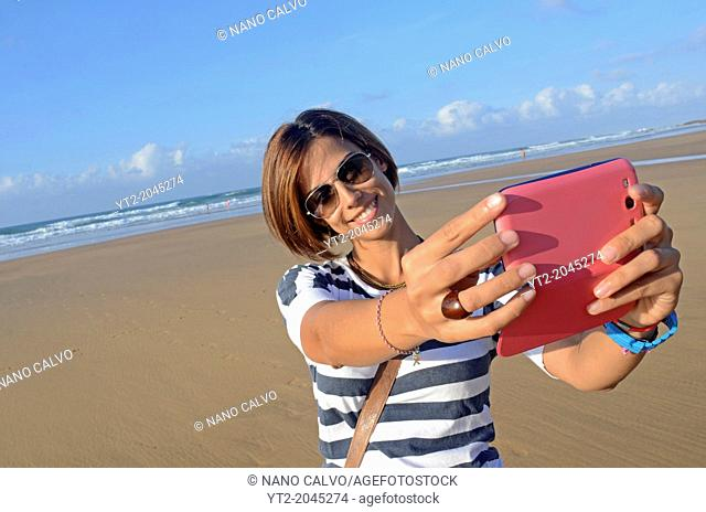 Attractive young woman on the beach, taking a selfie with mobile phone
