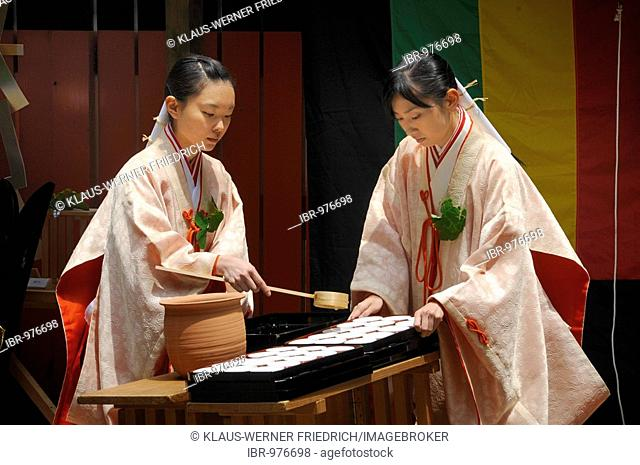 Shrine maidens handing out holy sake, rice wine, for the participants of the procession from the Shimogamo shrine to the Mikage shrine, Kyoto, Japan, Asia