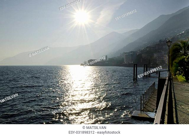 Lakefront with sunbeam and mountain with blue sky
