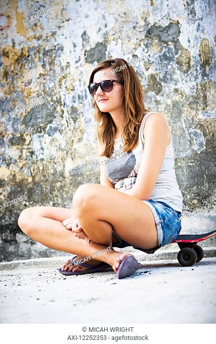 Young female tourist with a skateboard on a downtown street; Penang, Malaysia