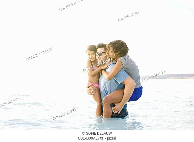 Young man wading in sea carrying wife and daughter, Tuscany, Italy