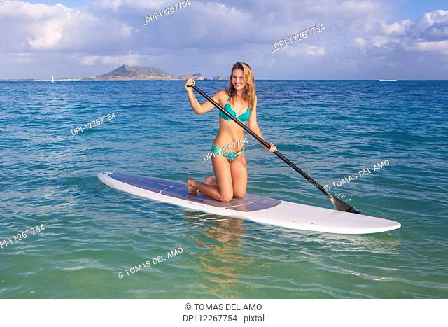Teenage girl with her paddle board; Kailua, Island of Hawaii, Hawaii, United States of America