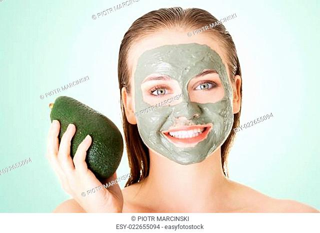 Beautiful woman with green avocado clay mask