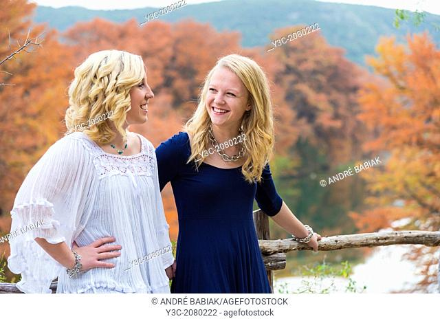 Outdoor portrait of two girls, 16 years old, caucasian ethnicity, standing outdoors with fall colored trees in the background, enjoying each others company