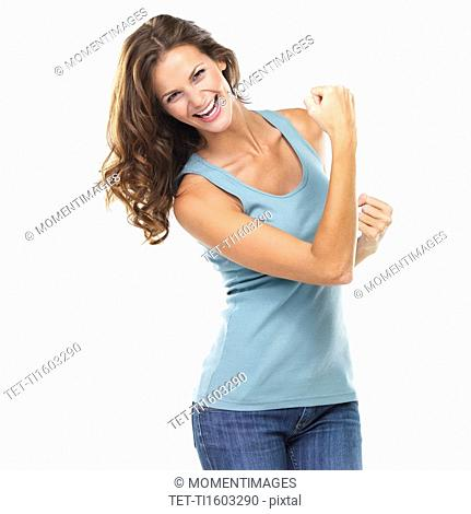 Studio portrait of attractive young woman with fists clenched