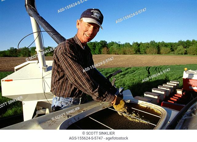 Agriculture - A farmer loads soybean seed into the seed hopper on his planter using a bulk loader during spring planting operations / IA