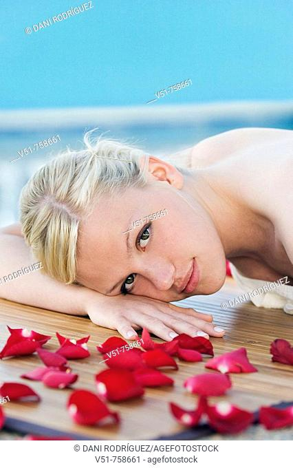 Young woman having a massage by the pool