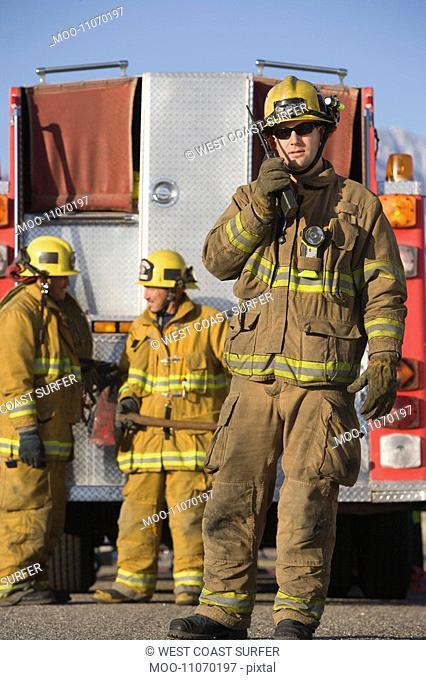 Firefighter using walkie talkie by fire engine