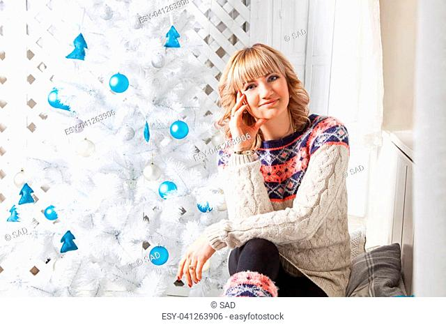 Portrait of a beautiful blonde woman in a warm and comfortable clothes