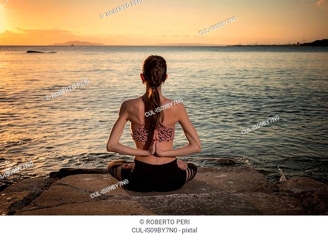Woman practising yoga at seaside