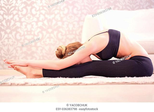 Push yourself. .Young woman doing stretching exercises by pushing forward her body to her legs