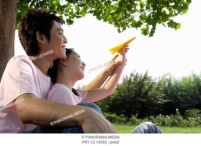Young lovers playing paper airplane on grass
