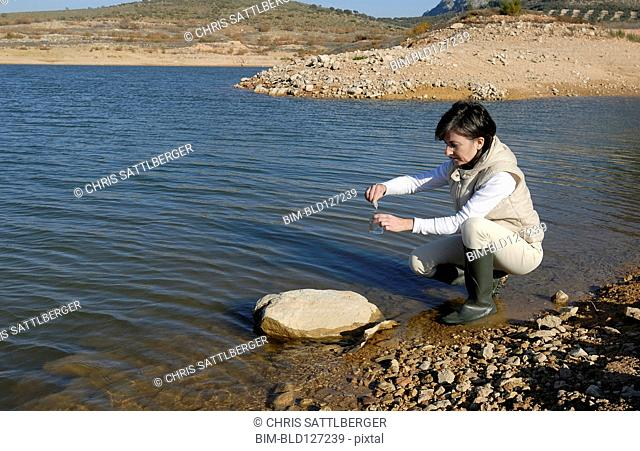 Female scientist taking water sample from lake side view