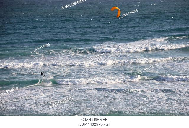 Aerial view kiteboarder kiteboarding on sunny windy ocean jumping wave