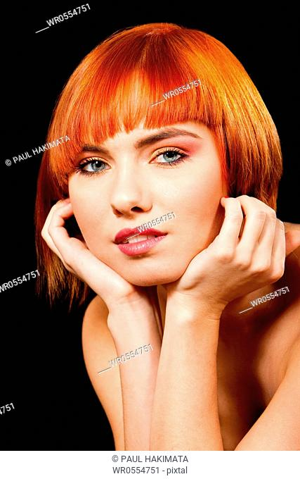 Face of a beautiful Caucasian redhead girl with glossy blue eyes supporting her head with hands, isolated