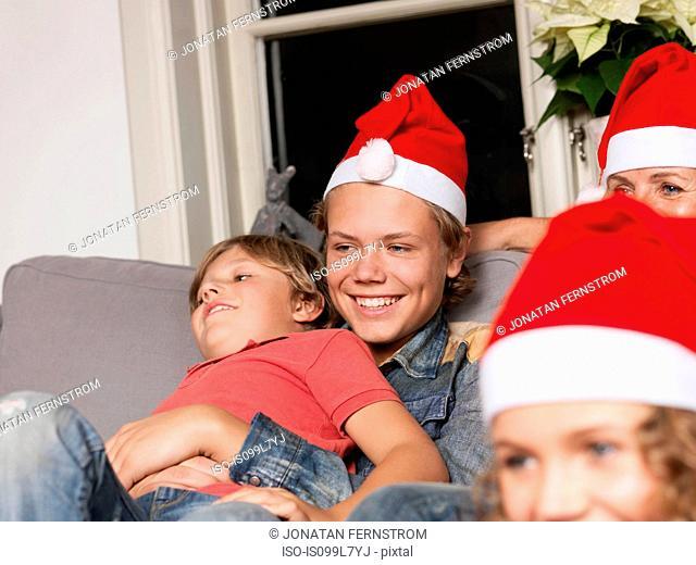 Family wearing Santa hats on sofa