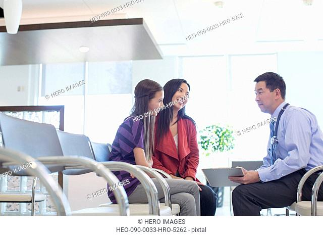 doctor reviewing medical chart with mother and daughter in waiting room