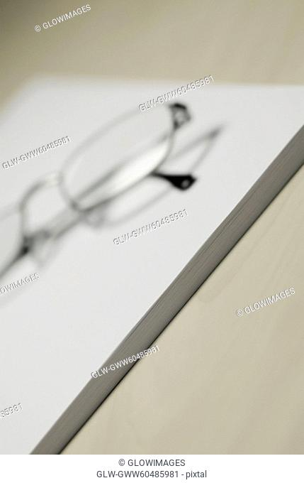 Close-up of eyeglasses and a notepad on the table