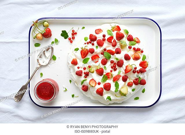 Pavlova with redcurrant, strawberry and fresh mint on serving tray