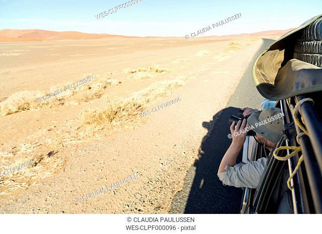 Namibia, Namib Desert, Namib Naukluft Park, Sossusvlei, man in a car looking through binoculars