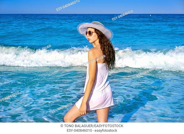 Girl with beach hat in sea shore profile view with summer white dress