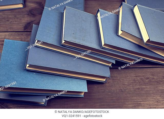 books in a blue cover on a brown wooden table, top view