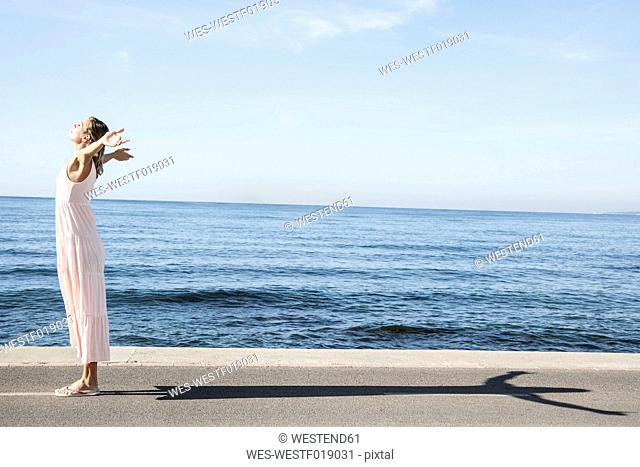 Spain, Mid adult woman standing at Atlantic Ocean with arms out
