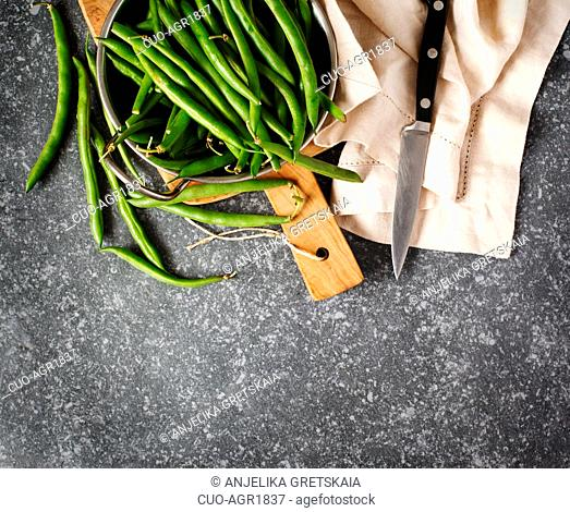 Green beans in bowl on dark background, top view, copy space