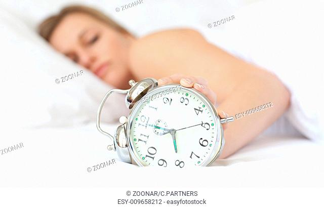 Blond woman holding an alarm clock