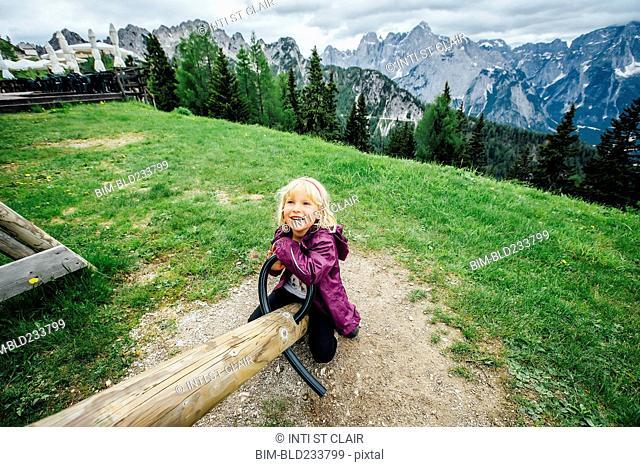 Caucasian girl on seesaw near mountain range, Tarvisio, Vienna, Austria