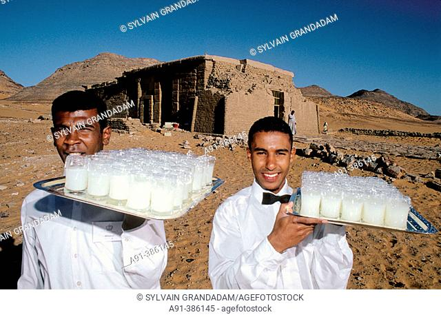 Waiters holding trays with refreshments for tourists aboard a cruise boat on Lake Nasser at Temple of Wadi El Sebua. Nubia. Egypt