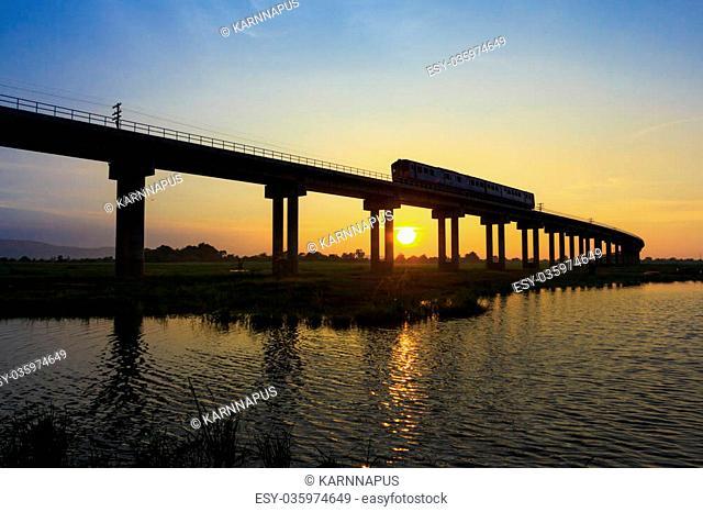 A train is crossing bridge at Pa Sak Jolasid Dam, Thailand in sunset time
