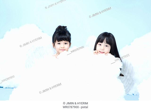 two little girls with looks of angels on the clouds