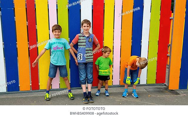 four brothers standing in front of a colorful batten fence