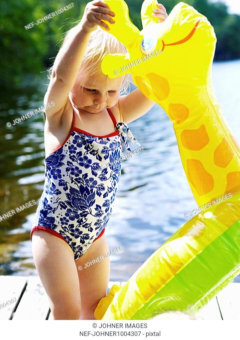 Scandinavia, Sweden, Girl (4-5) playing with Inflatable toy on pier, close-up