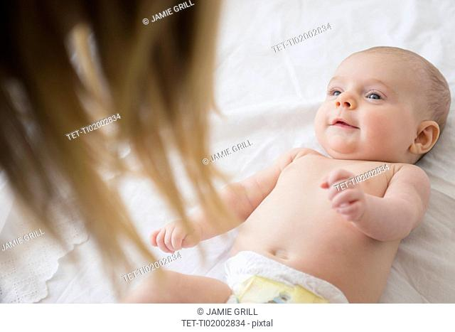 Mother playing with baby girl (2-5 months) on bed