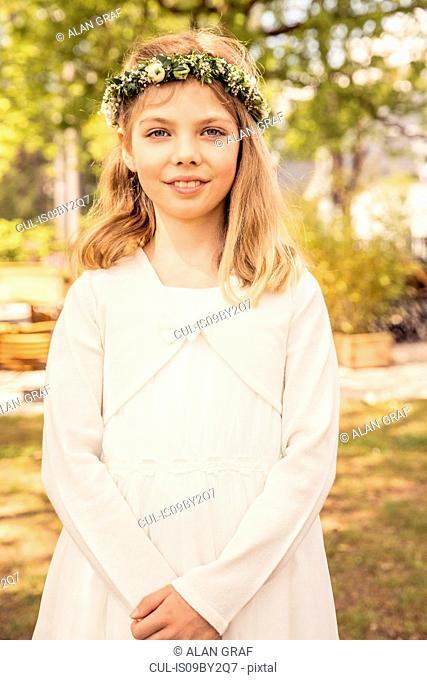 Girl wearing flower headdress in park, portrait