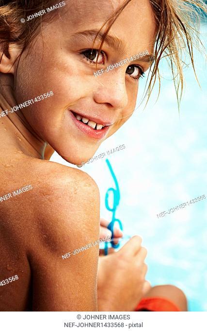 Portrait of boy in swimming pool drinking juice