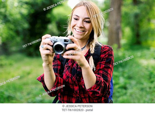 Young woman taking pictures in park