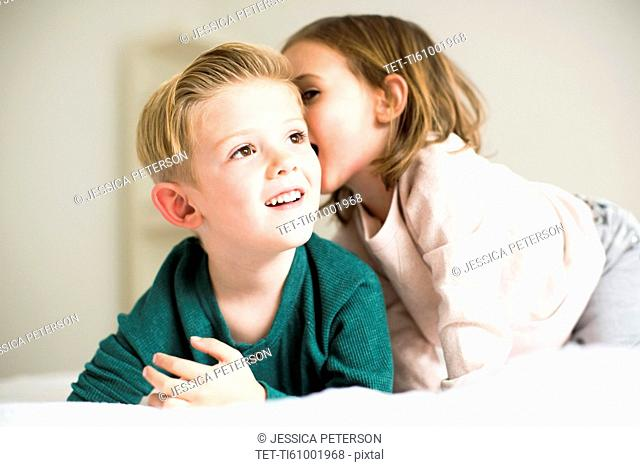 Siblings (2-3, 4-5) whispering in bedroom