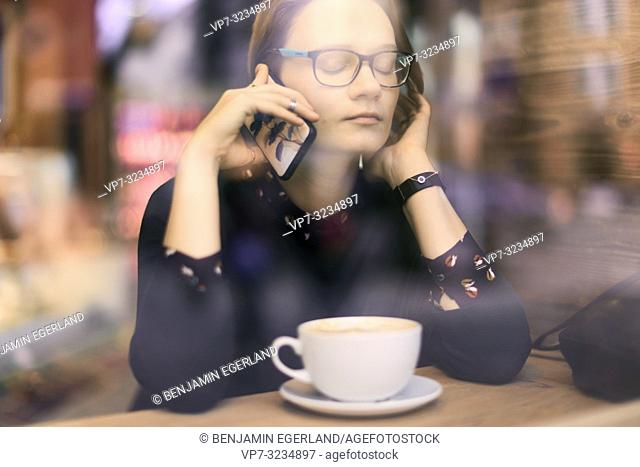 woman behind glass window calling with phone at ear, closed eyes, listening, next to coffee cup indoors in café Munich, Germany