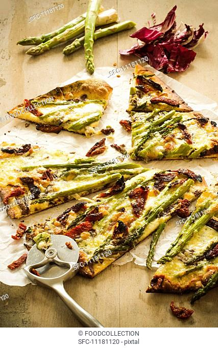 Sliced Asparagus and Sun Dried Tomato Pizza with a Pizza Cutter