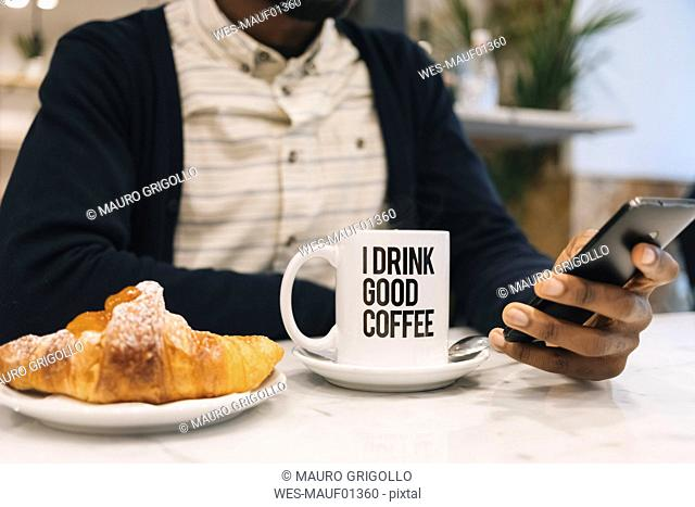 Close-up of man with croissant and cup of coffee in a cafe using cell phone