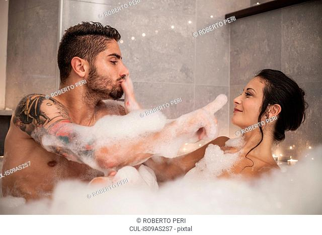 Young couple playing with bubbles in bubble bath