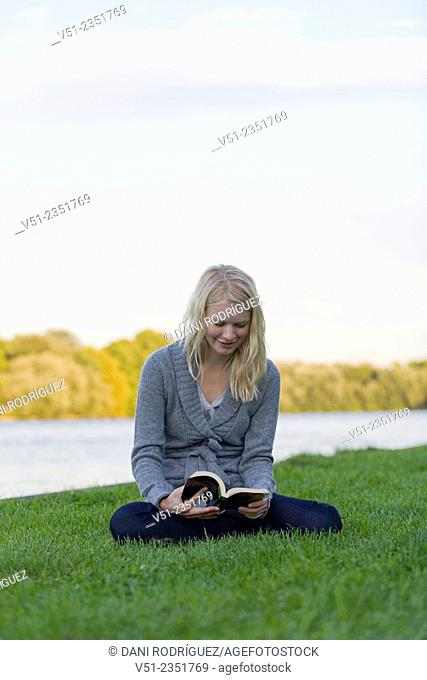 Young blonde woman reading a book by the river