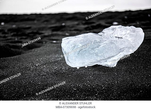 Ice block from the glacier on deep black sand in Jökulsárlón, Iceland