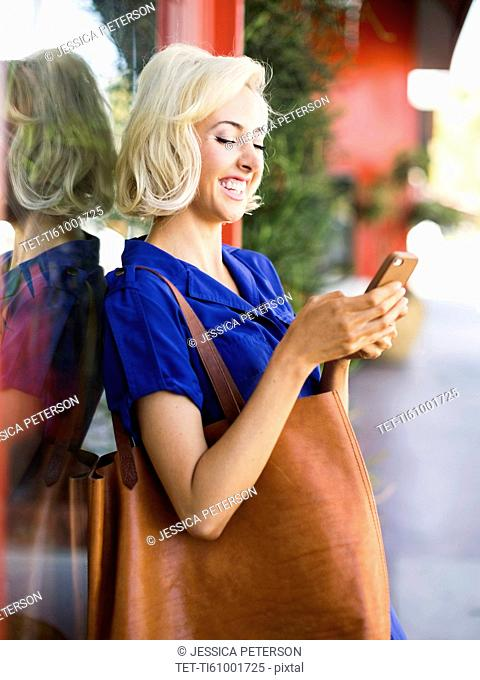 Woman leaning against window, using phone and smiling