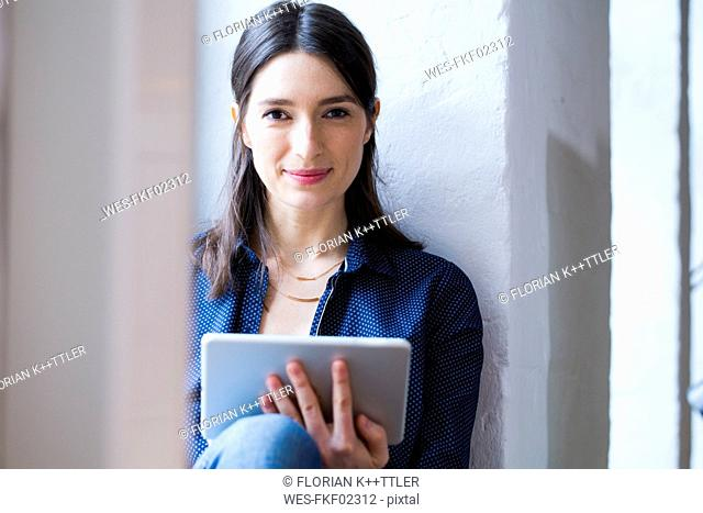 Portrait of confident woman with tablet at the window