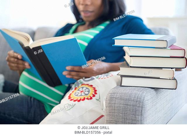 Black pregnant woman reading books on sofa